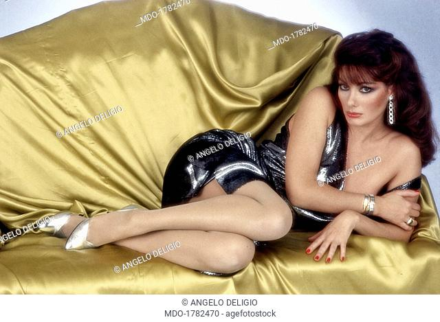French-born Italian actress Edwige Fenech posing with a seductive look lying on a sofa. Italy, 1983