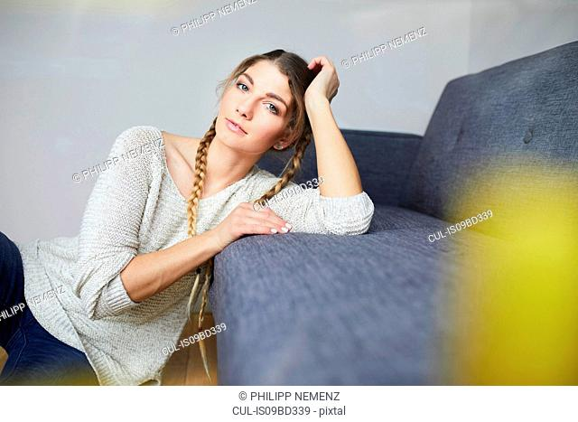 Young woman with plaits sitting on living room floor, portrait