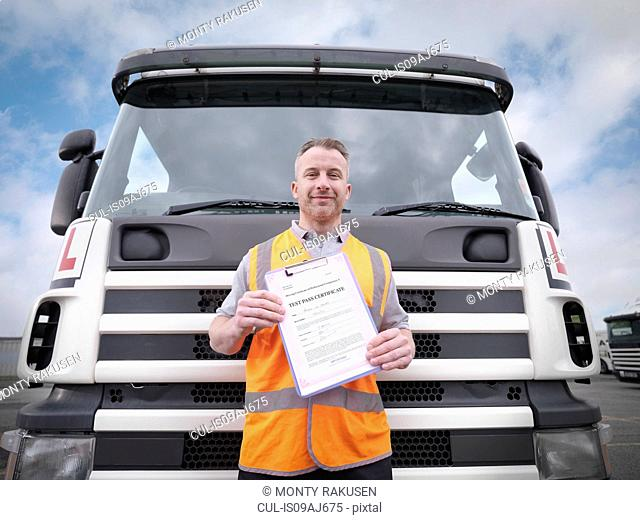 Portrait of trainee truck driver holding pass certificate