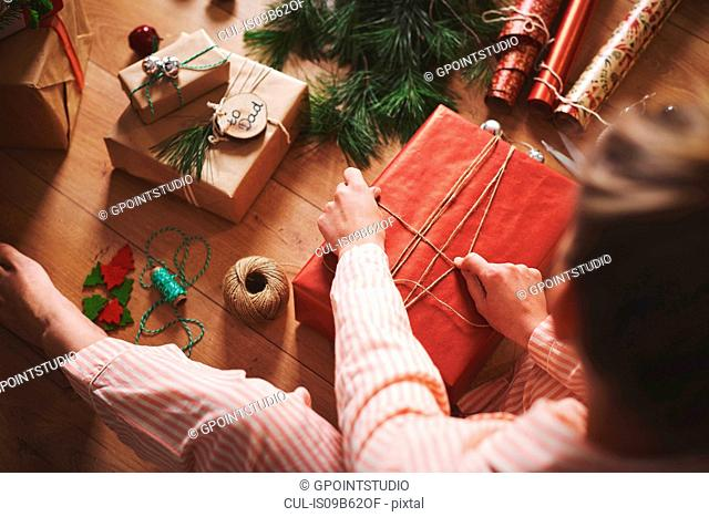 Woman wrapping christmas gift with twine
