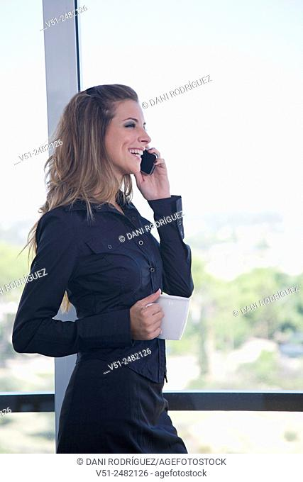 Businesswoman with coffee and phone by the window