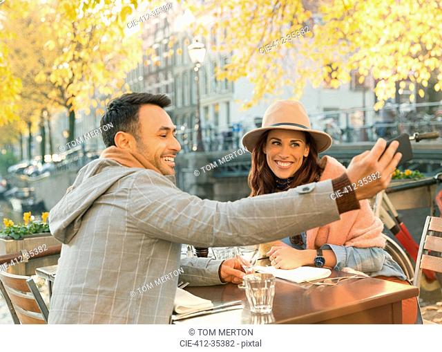 Young couple taking selfie with camera phone at autumn sidewalk cafe