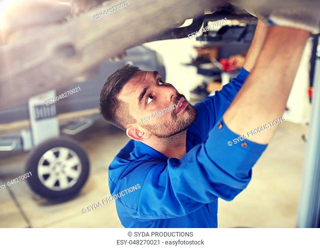 mechanic man or smith repairing car at workshop