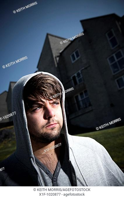 Young man wearing hoodie standing outside a block of flats