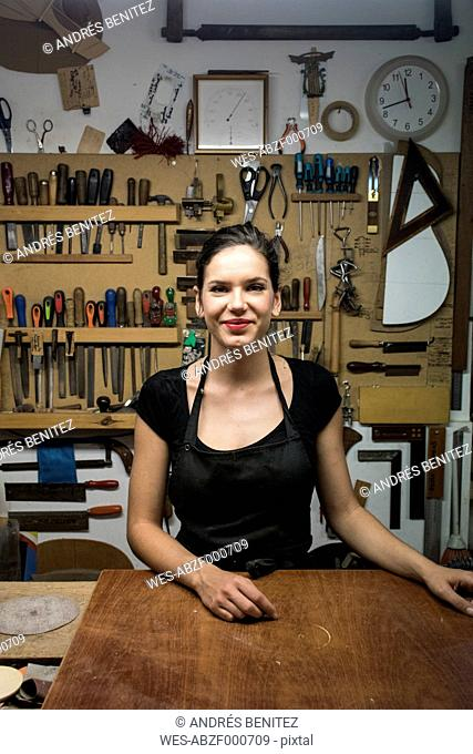 Portrait of smiling luthier in her workshop