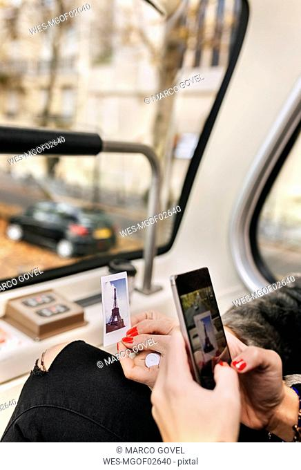 France, Paris, close-up of woman taking a picture on a tour bus
