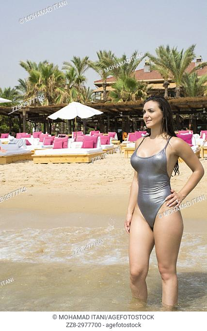 Beautiful woman in bikini standing on the beach lookinf away