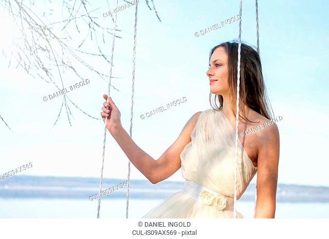 Woman wearing chiffon dress sitting on swing looking away