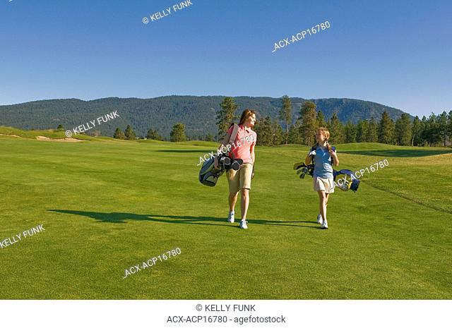 A young women and her junior golfer companion enjoy a beautiful day while walking down a fairway, on Two Eagles Golf Course in Westbank, British Columbia