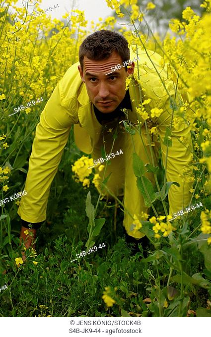 Mid adult man wearing a yellow suit sneaking up to something in a rape-field