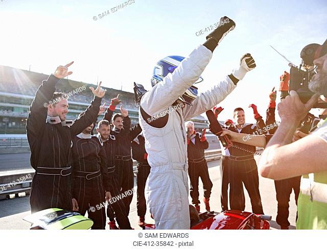 Formula one racing team and driver cheering, celebrating victory on sports track