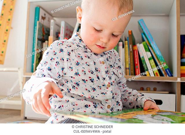 Female toddler reading book in playroom