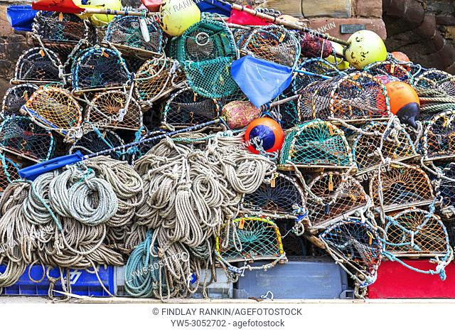 Lobster pots, fishing nets and fishing ropes piled at Beadnell harbour, Northumberland, England