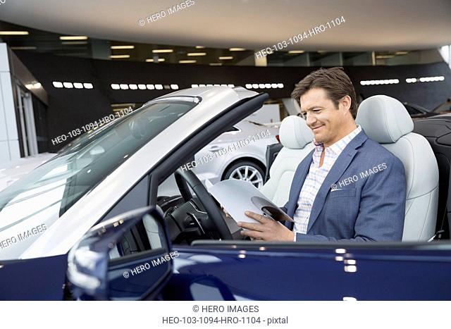Man looking at convertible in car dealership showroom
