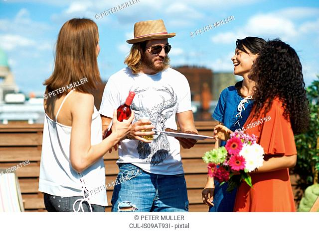 Male and female friends chatting at rooftop party