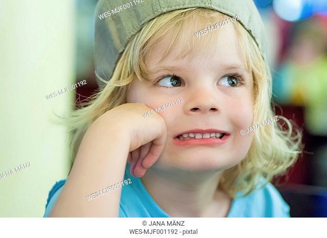 Blond boy wearing cap pulling faces