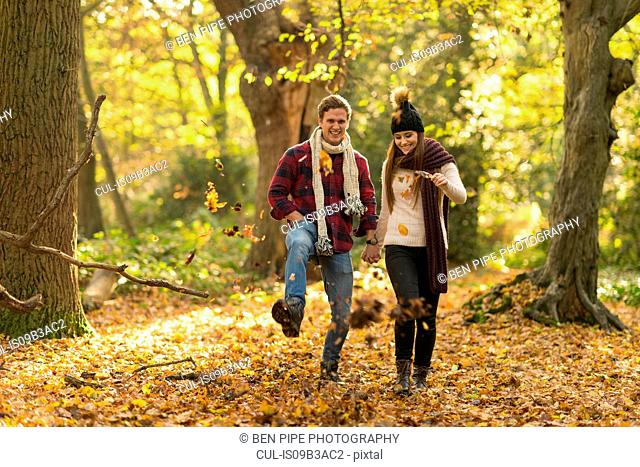 Young couple walking through forest, holding hands, smiling