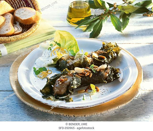 Sausages wrapped in vine leaves with pine nuts, tzatziki