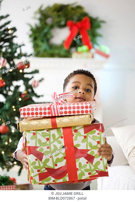 African American boy holding stack of Christmas gifts