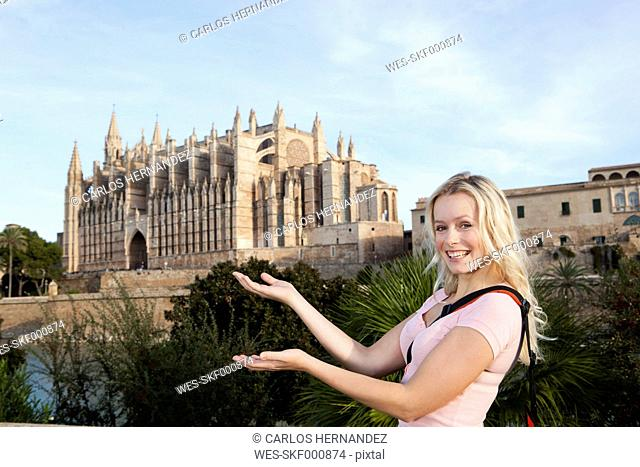 Spain, Mallorca, Palma, Young woman standing with St Maria Cathedral in background, smiling, portrait