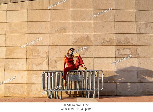 Spain, Barcelona, Montjuic, young woman wearing red jumpsuit sitting on barriers