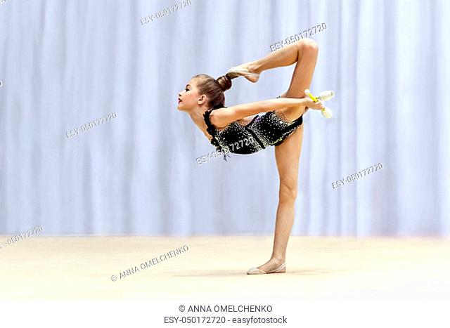 Little gymnast doing different difficult moves with a clubs on the stage, taking part in the rhythmic gymnastic competition, beautiful sport for girls