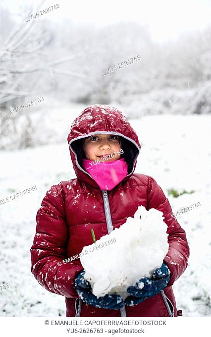 Little girl plays with snow