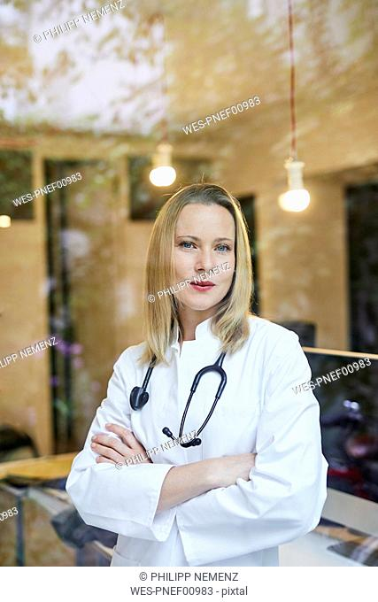 Portrait of female doctor with stethoscope behind windowpane