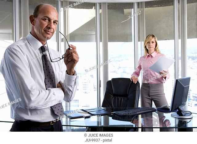 Mature businessman holding glasses, young woman by desk in background, portrait