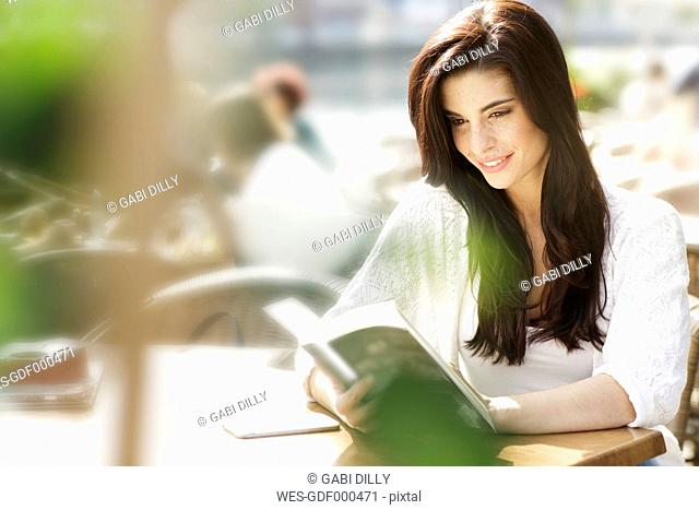 Young woman reading a book at a pavement cafe