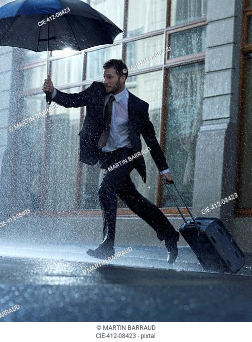 Businessman with suitcase and umbrella crossing rainy street