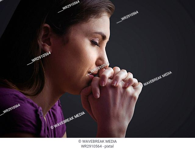Woman praying against dark grey background