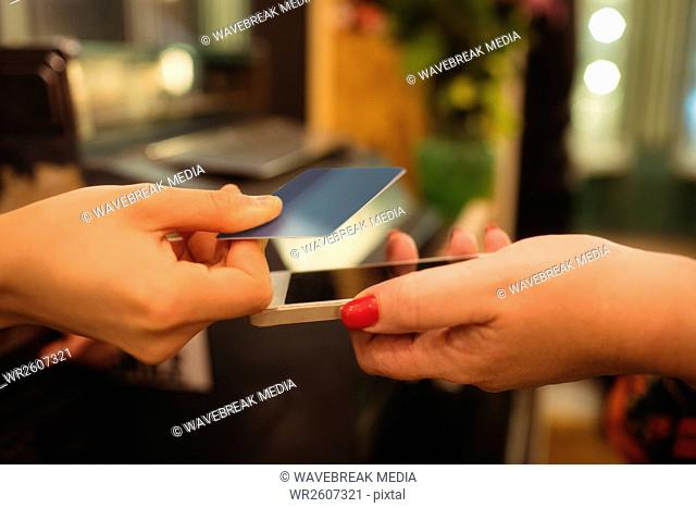 Customer giving her phone and credit card to cashier
