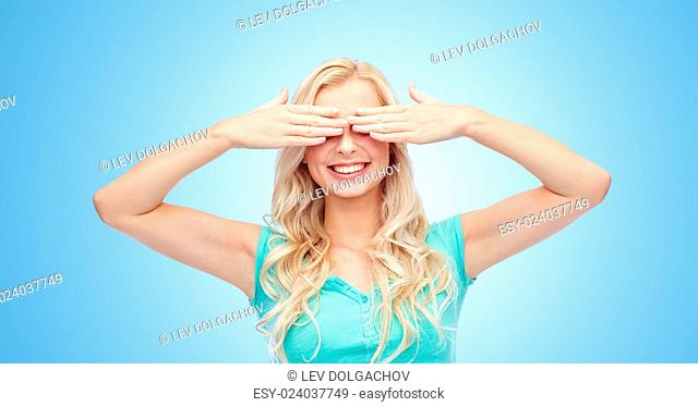 emotions, expressions and people concept - smiling young woman or teenage girl covering her eyes with palms over blue background