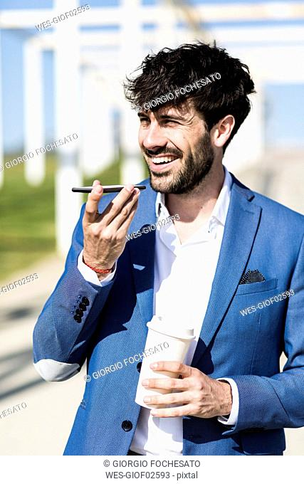 Happy young businessman with smartphone and takeaway coffee outdoors