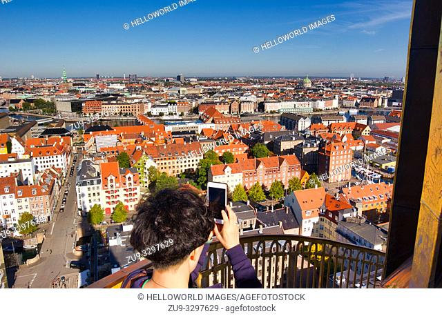 Female Asian tourist taking photograph on smartphone from the external staircase of Church of our Saviour (Vor Frelsers Kirke), Christianshavn, Copenhagen
