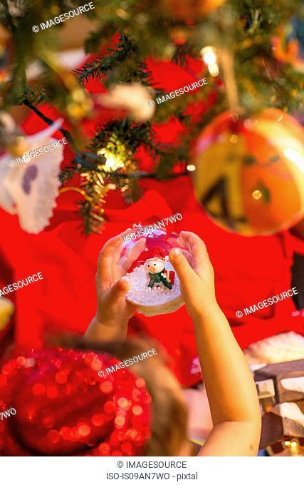 Little girl holding snow globe ornament in hand