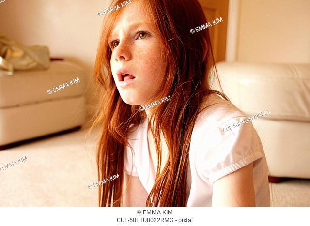 Girl sitting on living room floor