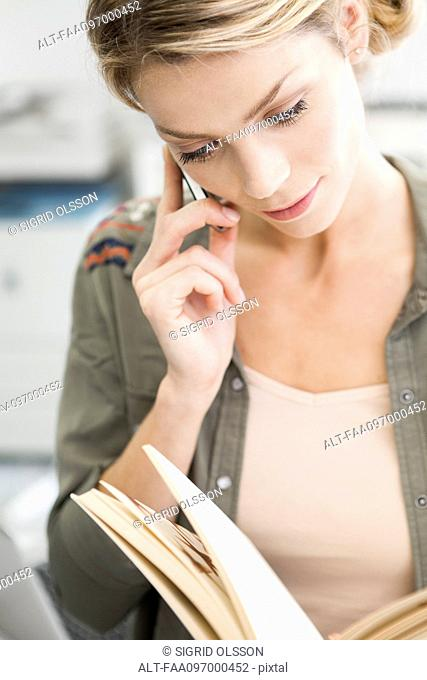 Woman using cell phone while reading book