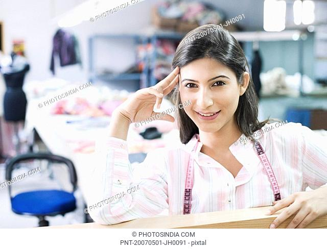 Portrait of a female fashion designer smiling with a tape measure around her neck