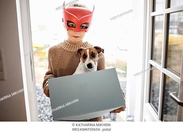 Portrait of boy wearing Superhero mask with Jack Russel Terrier in