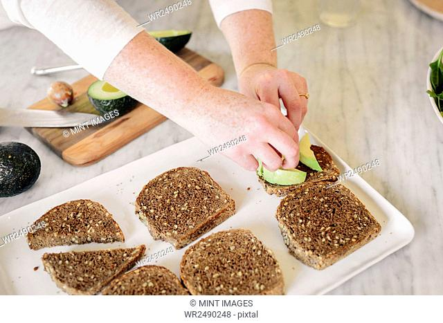 A woman preparing a sandwich with slices of brown bread and sliced avocado