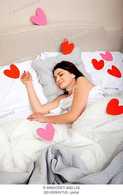 Woman in bed with heart shapes on bedclothes