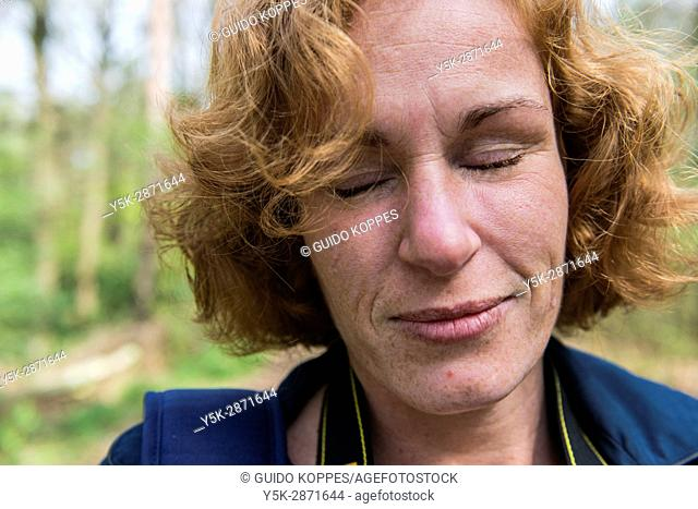 Regte Heide, Riel, Netherlands. Redheaded woman enjoying the quiet, while strolling through a nature reserve forrest