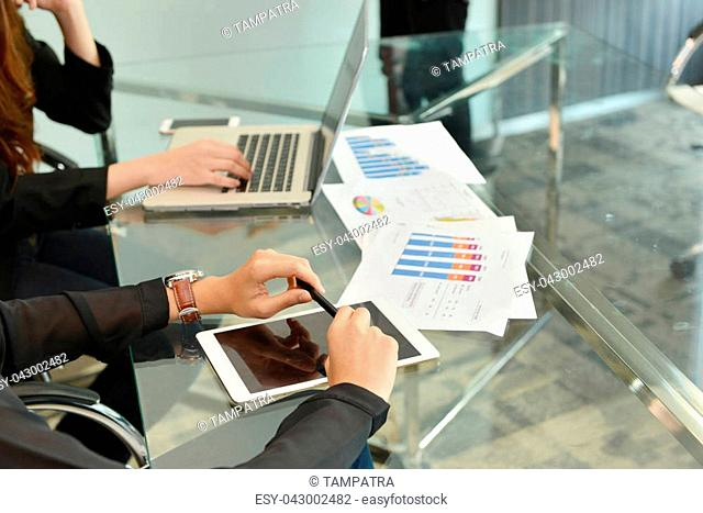 Technology equipment with laptop, business documents on meeting table