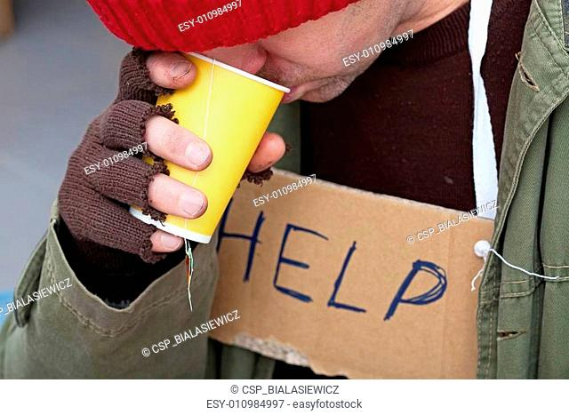 Homeless man drinking hot tea