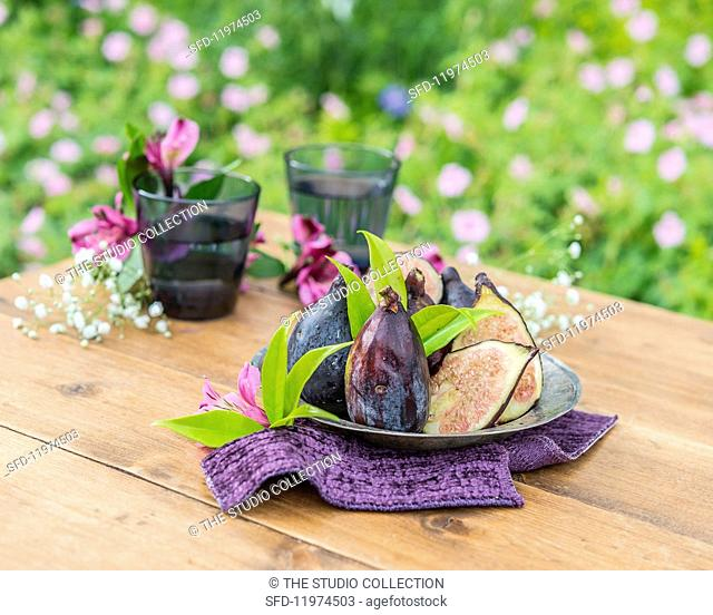 Purple figs on a pewter plate on a garden table