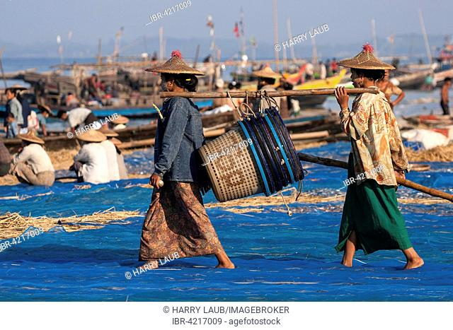 Local women wearing a straw hat, carrying empty fish baskets to the sea, behind fishing boats on the beach of the fishing village Ngapali, Thandwe
