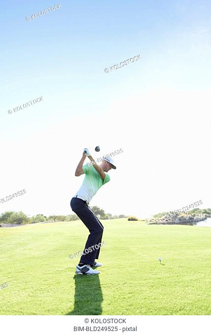 Caucasian man teeing off on golf course