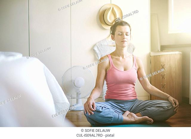 Mid adult woman in yoga lotus position in bedroom